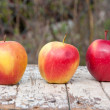 Three red apples on a wooden table — Stock Photo