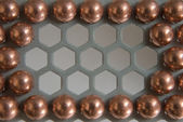 Little balls in metallic honeycomb pattern — Stockfoto
