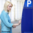Woman Putting Money In A Parking Ticket Machine - Zdjcie stockowe