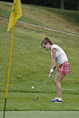 Woman in her mid 20s playing golf — Stock Photo