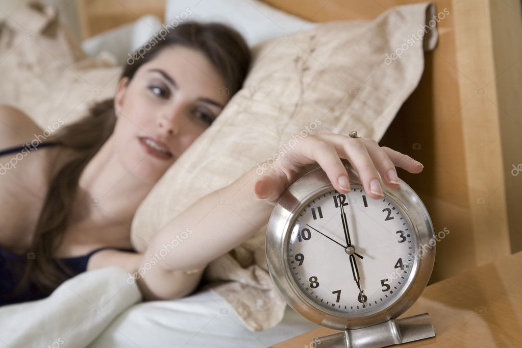 Woman in early waking up to an alarm clock — Photo #10951729
