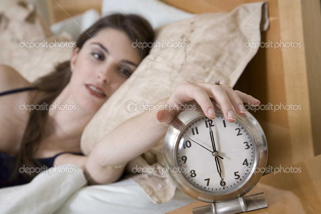 Woman in early waking up to an alarm clock — Stockfoto #10951729