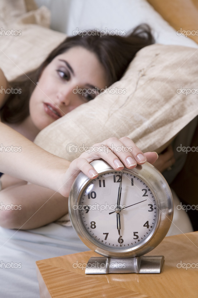 Woman in early waking up to an alarm clock — Stockfoto #10951733