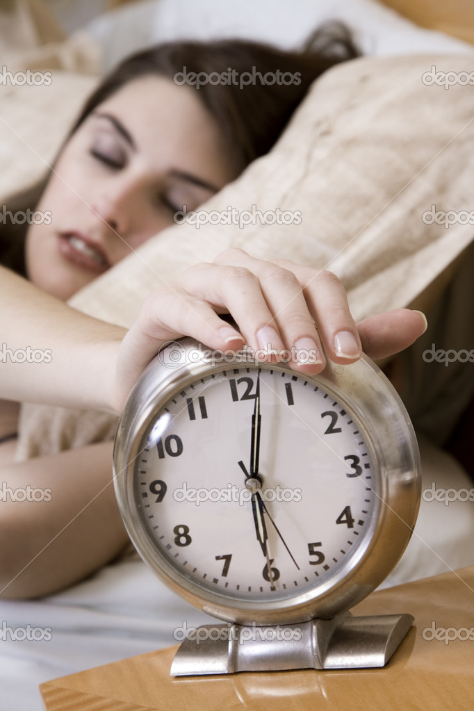 Woman in early waking up to an alarm clock — Stock fotografie #10951740