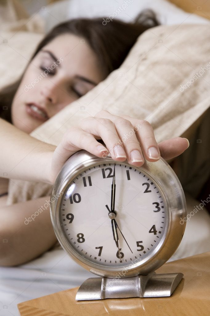 Woman in early waking up to an alarm clock — Lizenzfreies Foto #10951740