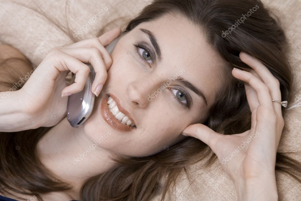 Young caucasian woman layin gin bed talking on the phone — Stock Photo #10951767