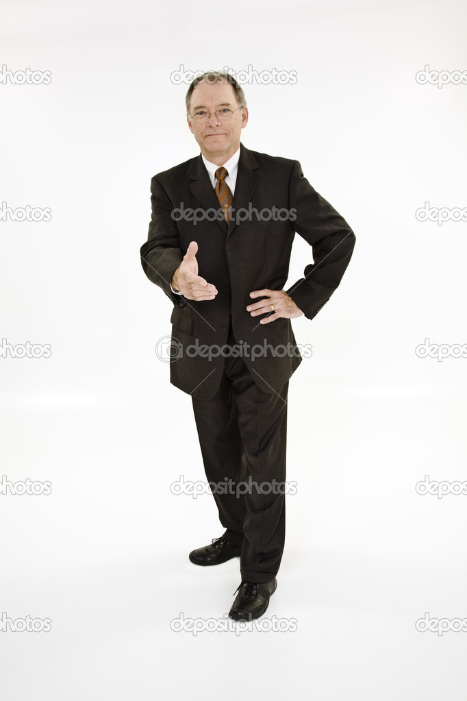 A caucasian businessman with a receding hairline wearing a black business suit and white shirt. He is shown on a white background reaching out to shake someone's hand and is smiling. — Stock Photo #11316411