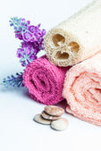 Spa towels rolls, flower and stones. — Stock Photo