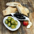 Green olives with fresh bread and herbs — Stock Photo