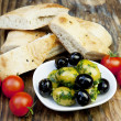 Green olives with fresh bread and herbs — Stock Photo #10841438
