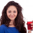 Beautiful smiling brunette woman is drinking red juice - Stock Photo