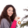 Royalty-Free Stock Photo: Beautiful brunette woman is decorating a christmas tree