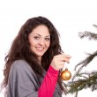 Beautiful brunette woman is decorating a christmas tree — Stock Photo #11725980