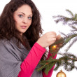 Beautiful brunette woman is decorating a christmas tree — Stock Photo #11726001