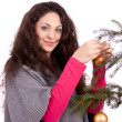 Stock Photo: Beautiful brunette woman is decorating a christmas tree