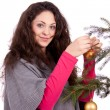 Beautiful brunette woman is decorating a christmas tree — Stock Photo