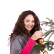 Beautiful brunette woman is decorating a christmas tree — Stock Photo #11726023