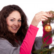 Beautiful brunette woman is decorating a christmas tree - Stock Photo