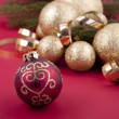 Beautiful golden christmas decoration on red background — Stock Photo