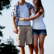 Young woman and man is walking on a road in summer outdoor — Stock Photo