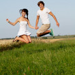 Young happy couple jumping outside in summer — Stock Photo
