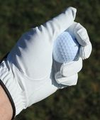 Golf ball in goved hand — Stock Photo
