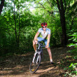 Young man stands in the wood with bike — Stock Photo