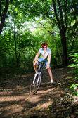 Jeune homme se trouve dans le bois avec vélo — Photo
