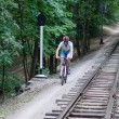 Man rides in the forest near the railroad - Stock Photo
