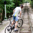 Byciclyst climbing on the railroad — Stock Photo