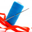 Threads, a needle and a satiny tape. On a white background. — Stock Photo