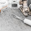 Stock Photo: Sewing machine, threads and thimbles on fabric.