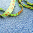 Measuring tape on a fabric (jeans). - Photo