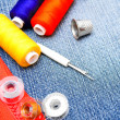 Threads, thimbles, zipper lock on a fabric. - Stock Photo