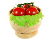 Tomatoes and greens in a wooden cup. — Stock Photo