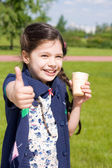 Girl with ice cream shows thumbs up — Stock Photo