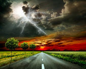 Asphalt road and lightning — Stock Photo