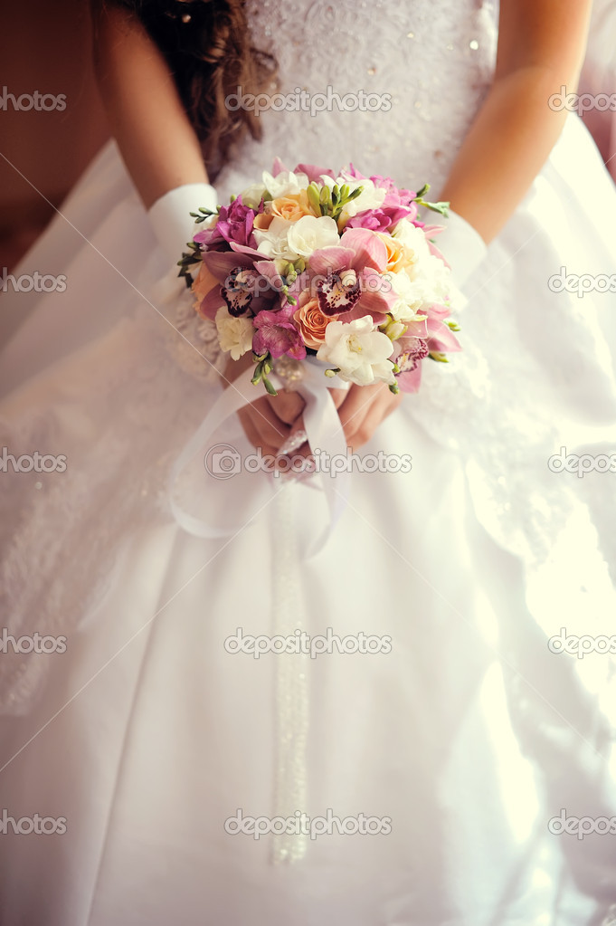 Against a wedding dress of a hand of the bride hold a bouquet — Stock Photo #11089529