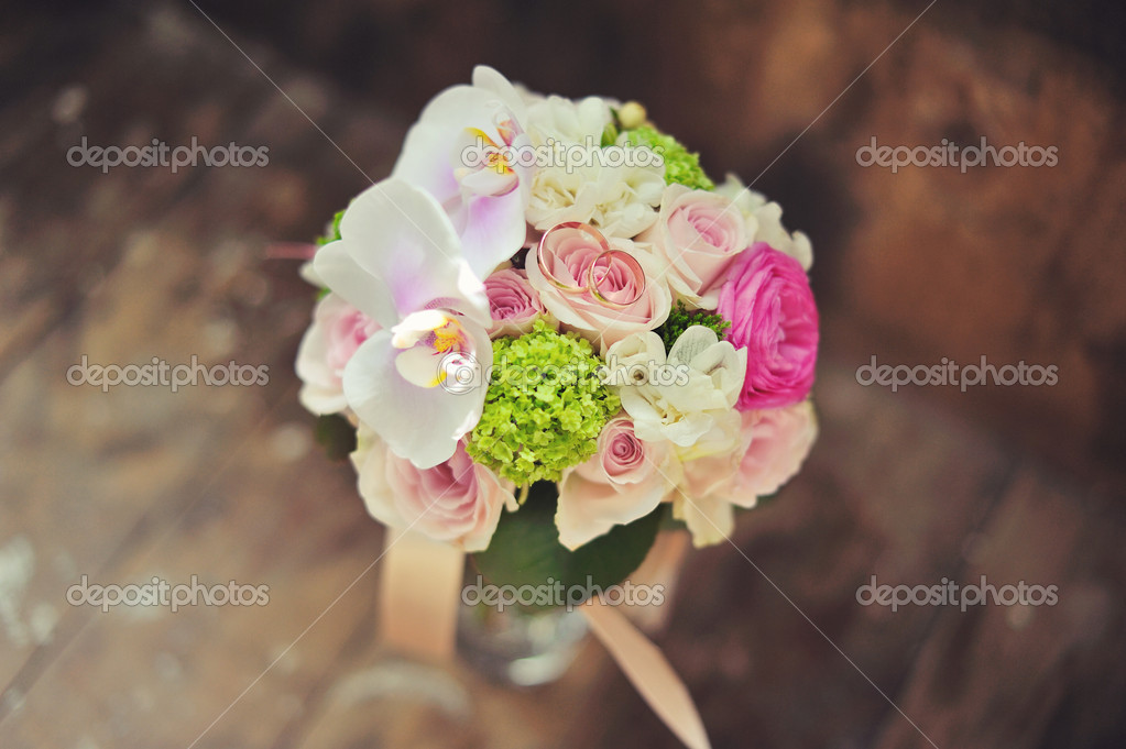 Against a wedding dress of a hand of the bride hold a bouquet — Stock Photo #11109849