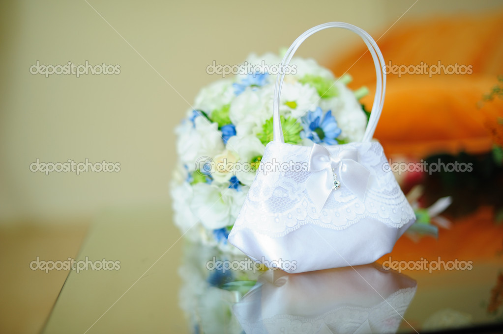 Against a wedding dress of a hand of the bride hold a bouquet — Stock Photo #11111115