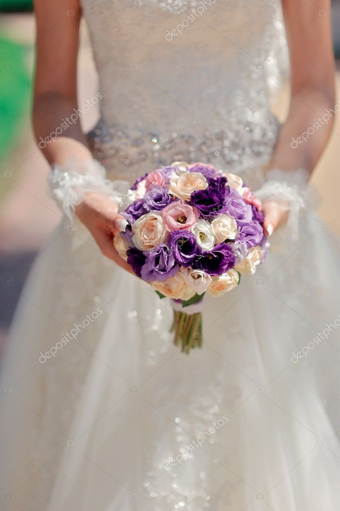 Against a wedding dress of a hand of the bride hold a bouquet  Stock Photo #11782930