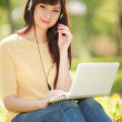 Cute woman in earphones with white laptop in the park — Stock Photo #10740849