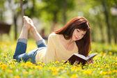 Joven leyendo un libro en el parque con flores — Foto de Stock