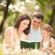 Happy mother, father and daughter read a book in the park — Stock Photo #11519962