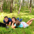 Young with a laptop in the forest — Stock Photo