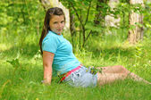 The girl is sitting on the edge of the forest — Stock Photo