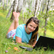 Young girl with laptop in the forest — Stock Photo