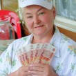 Stock Photo: A woman with five thousand bills in the hands of