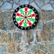 The Dartboard on rock wall background — Stock Photo
