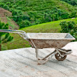 Old wheelbarrow on mountain background — Stock Photo #10848326